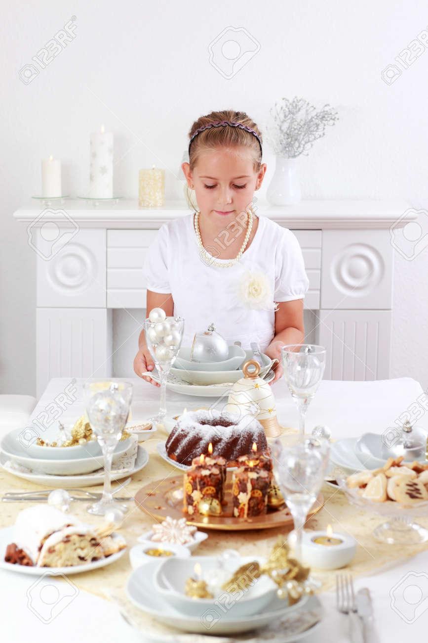 Cute girl setting table for Christmas Stock Photo - 11497024