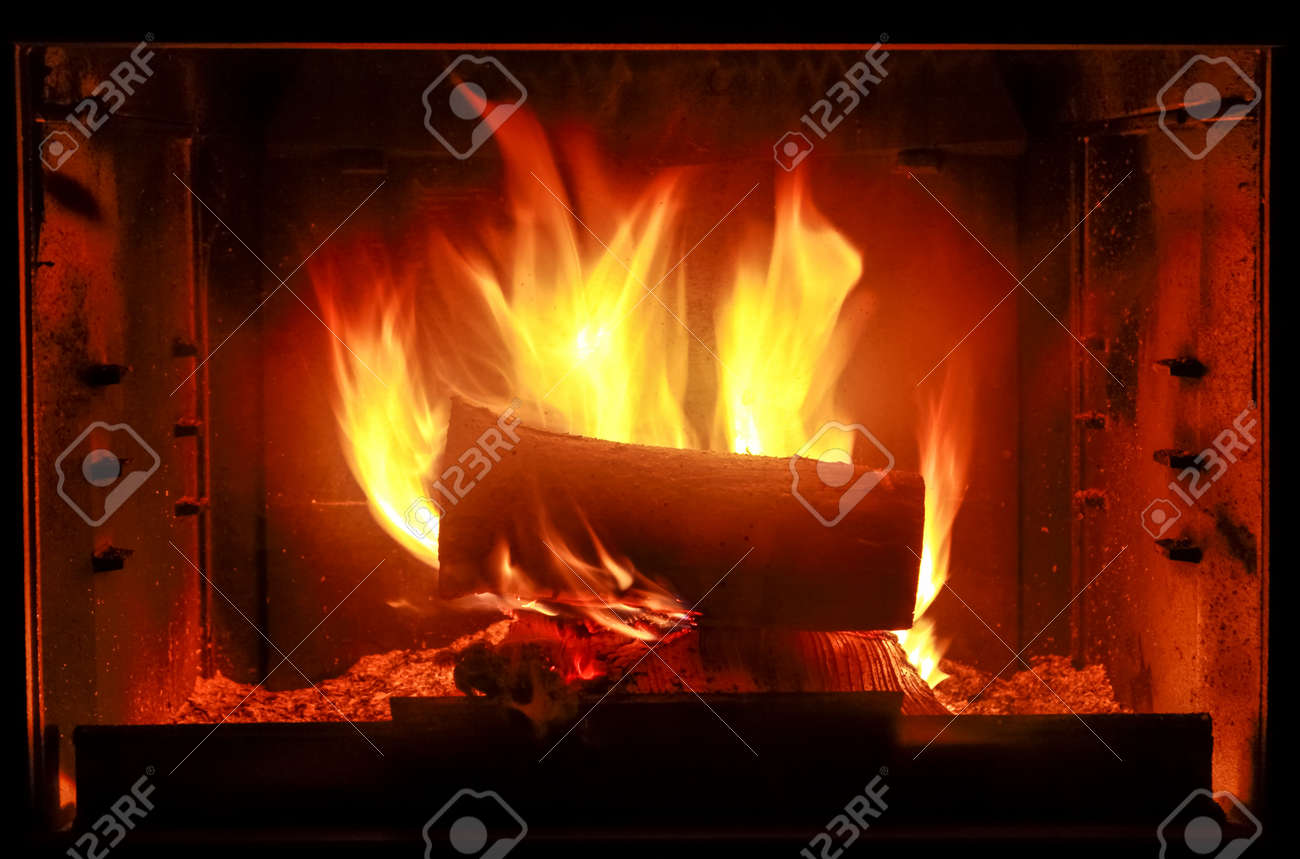fireplace with wood and fire resistant glass doors stock photo