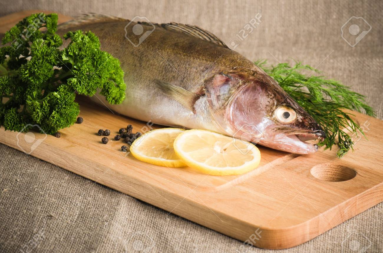 Pike perch on a wooden kitchen board, it is isolated on white Stock Photo - 15563140