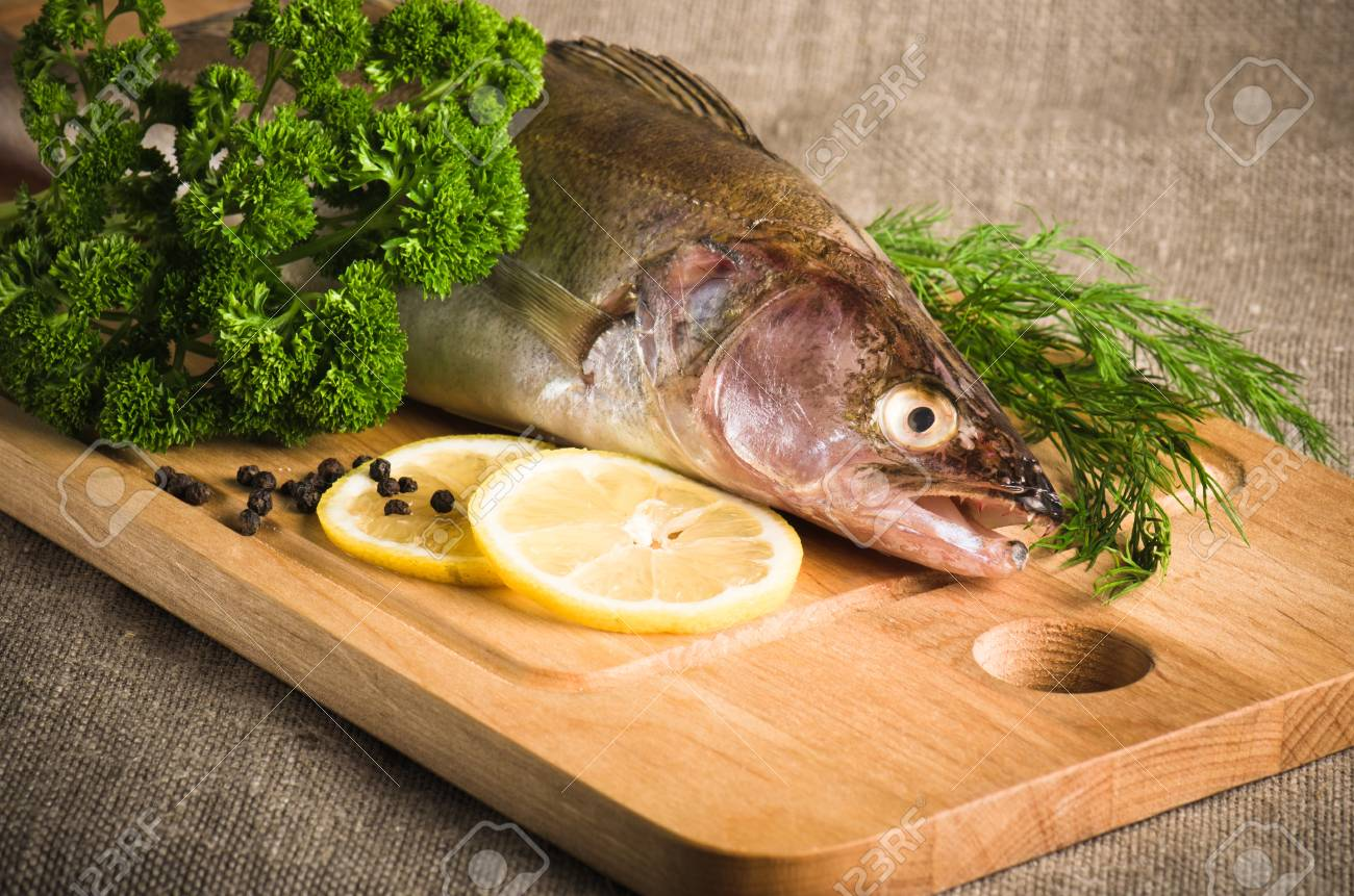 Pike perch on a wooden kitchen board, it is isolated on white Stock Photo - 15563196