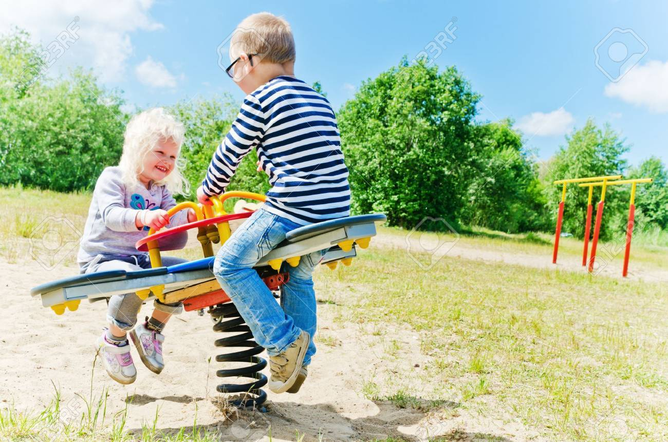 Boy and girl swinging on a swing Stock Photo - 20366451