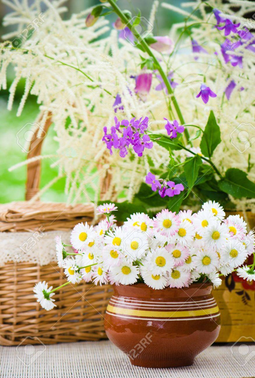 Bouquet of wild flowers in a pot at the table Stock Photo - 21449381