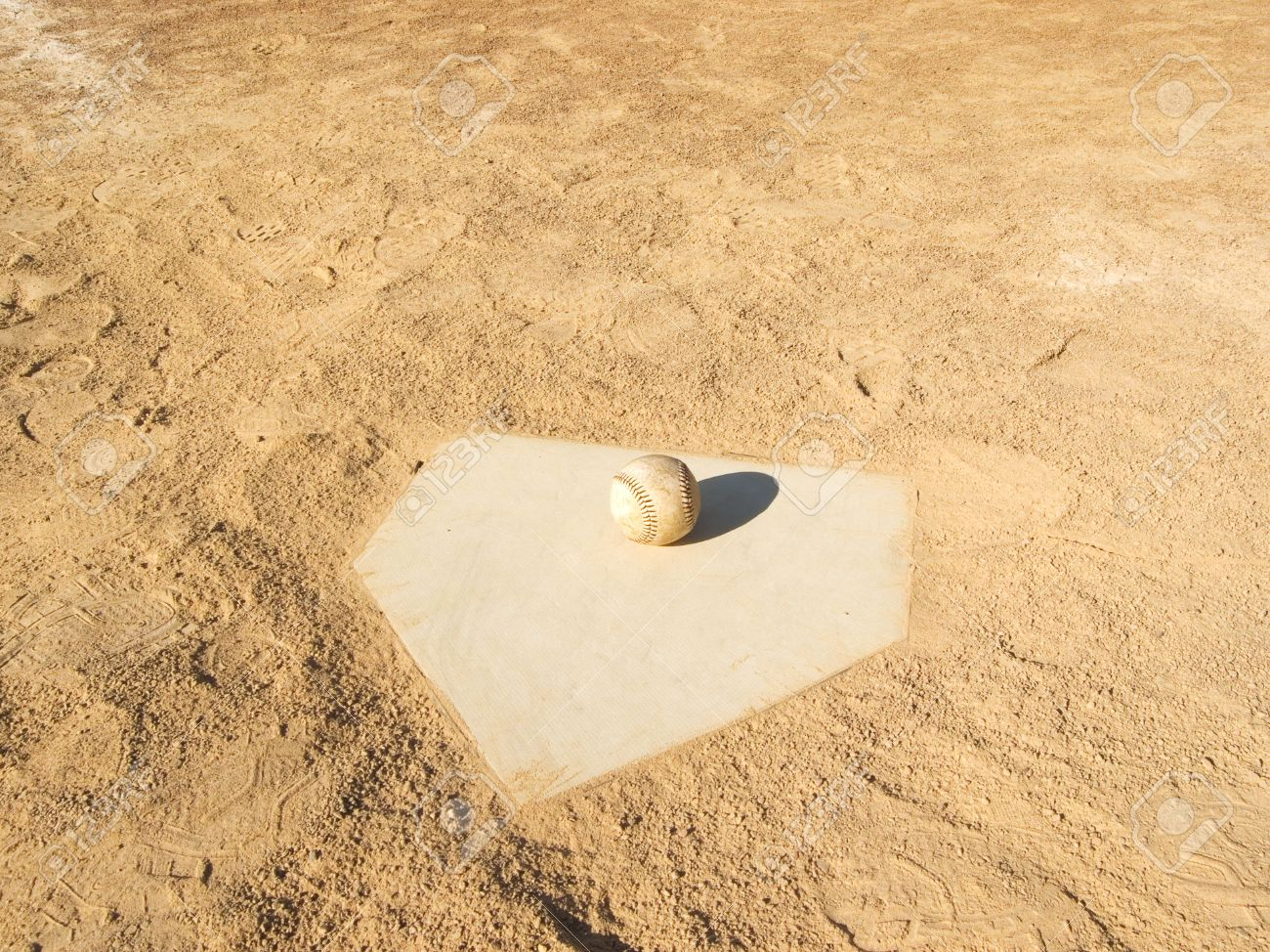 home plate on a baseball field with a baseball set on it stock
