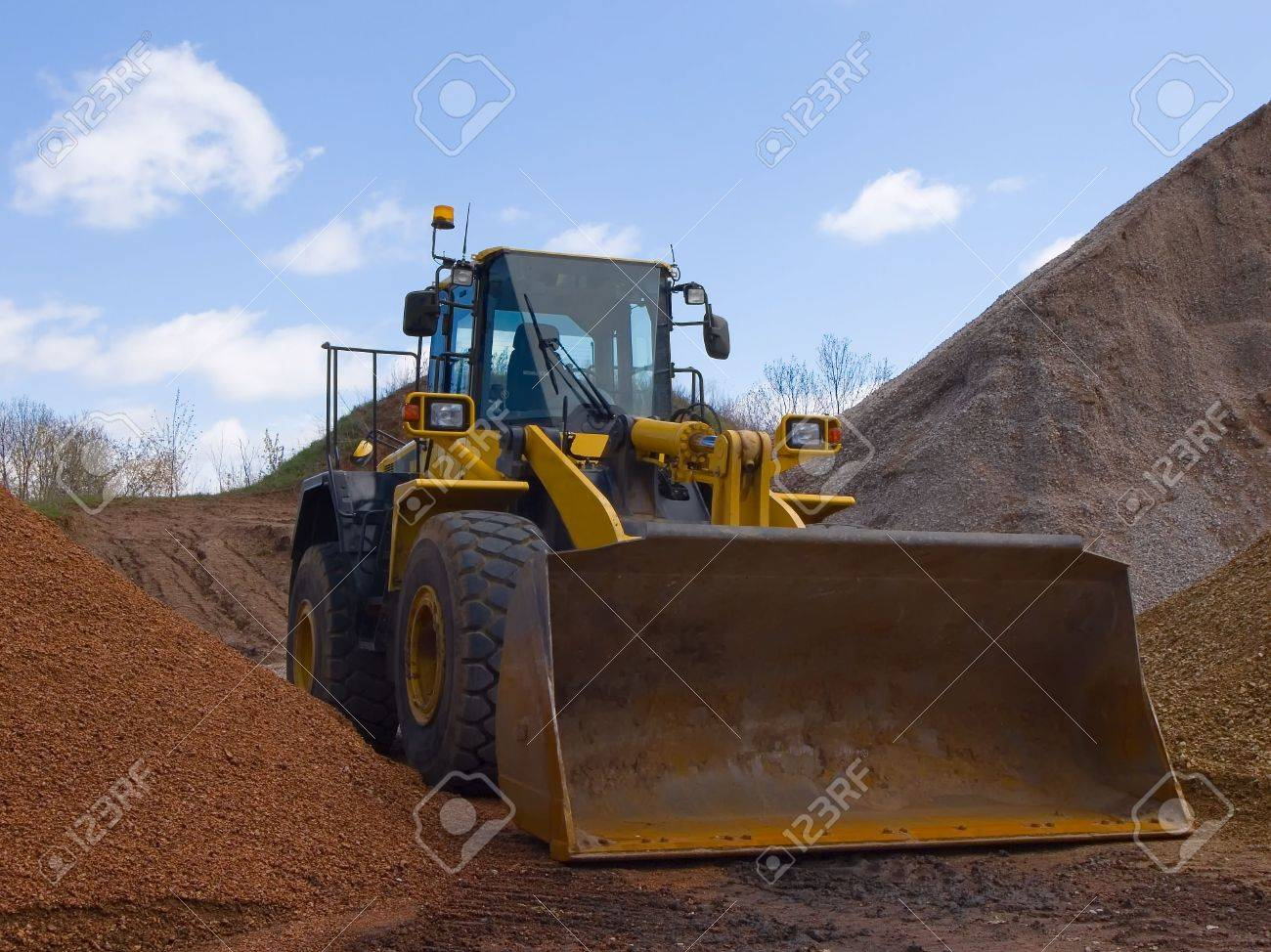 front end loader surrounded by hills of dirt and stone stock photo