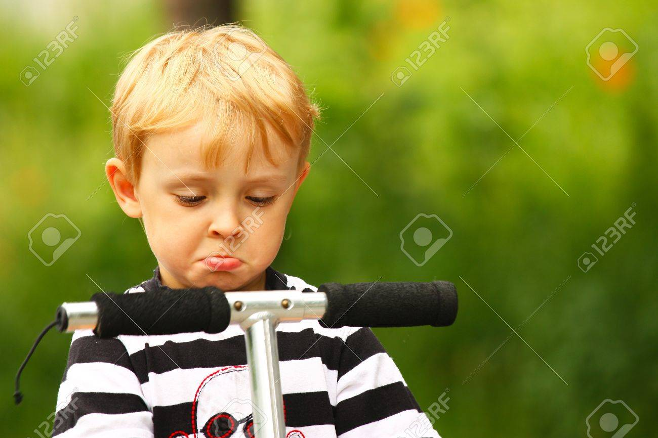 Angry kid on a scooter in outdoor Stock Photo - 15199112