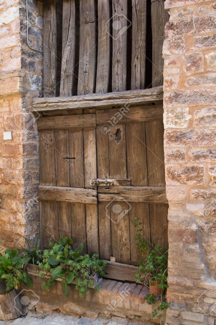 Antica porta di legno in una vecchia città italiana. (Spello, Umbria,  Italia)