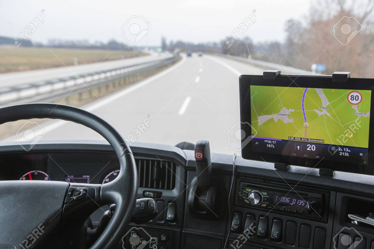 View of highway traffic through the windshield of the truck cab. Navigation is mounted on the dashboard. - 37927057
