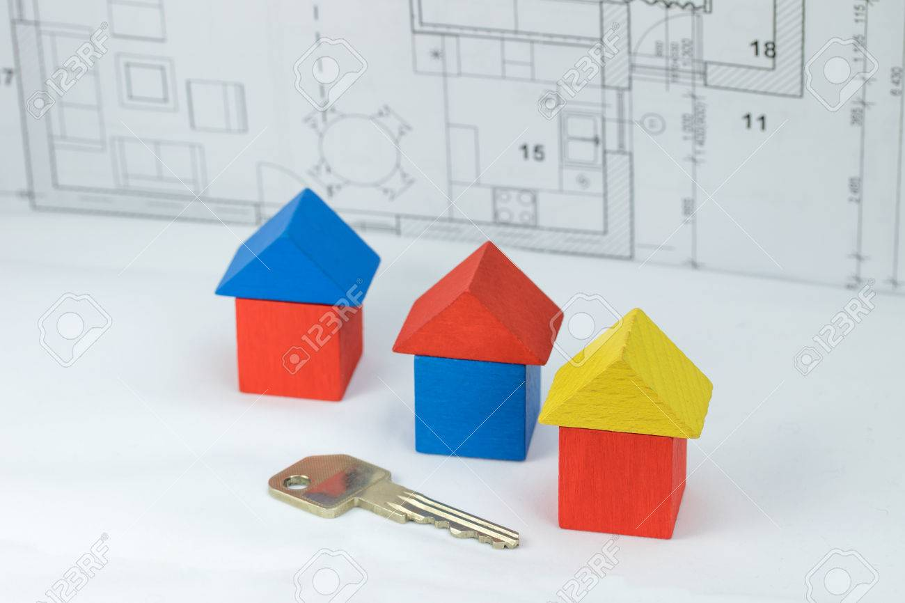 Three houses made of wooden multicolored shapes are standing three houses made of wooden multicolored shapes are standing in front of the blueprint of the malvernweather Choice Image