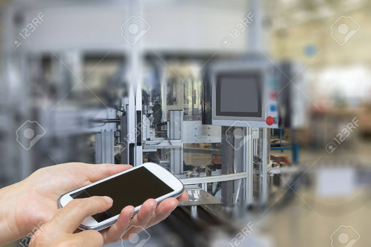 Female is using the smart phone. The automatic production line is in the background. The edges of the pictures are deliberately blurred. - 44393073
