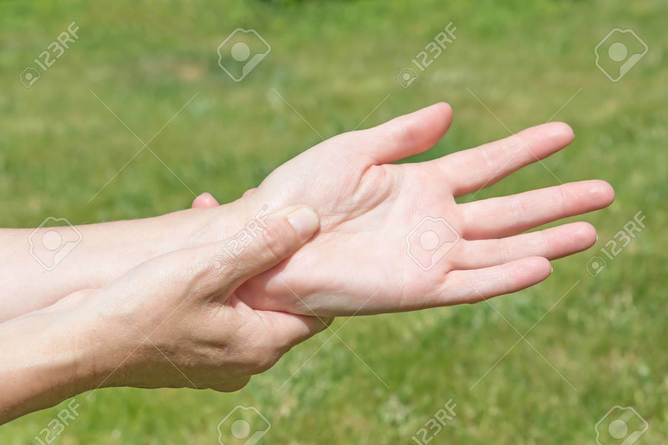 Female hands showing carpal tunnel syndrome problem outdoors - 60225692