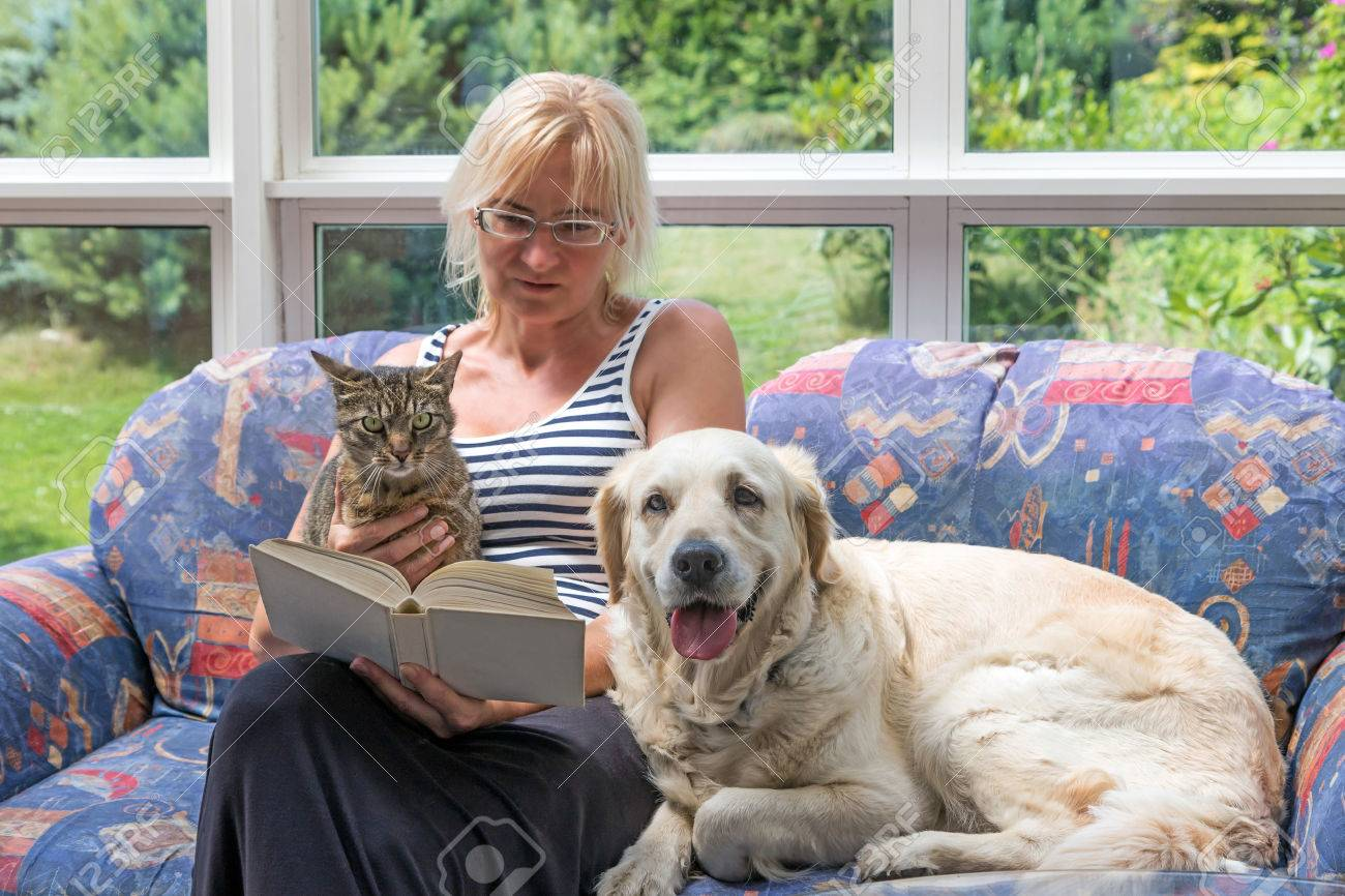 Blond middle aged woman is sitting on a couch and reading a book. Striped cat and Golden Retriever dog are sitting with her together. The pets are looking at the camera. - 72098023