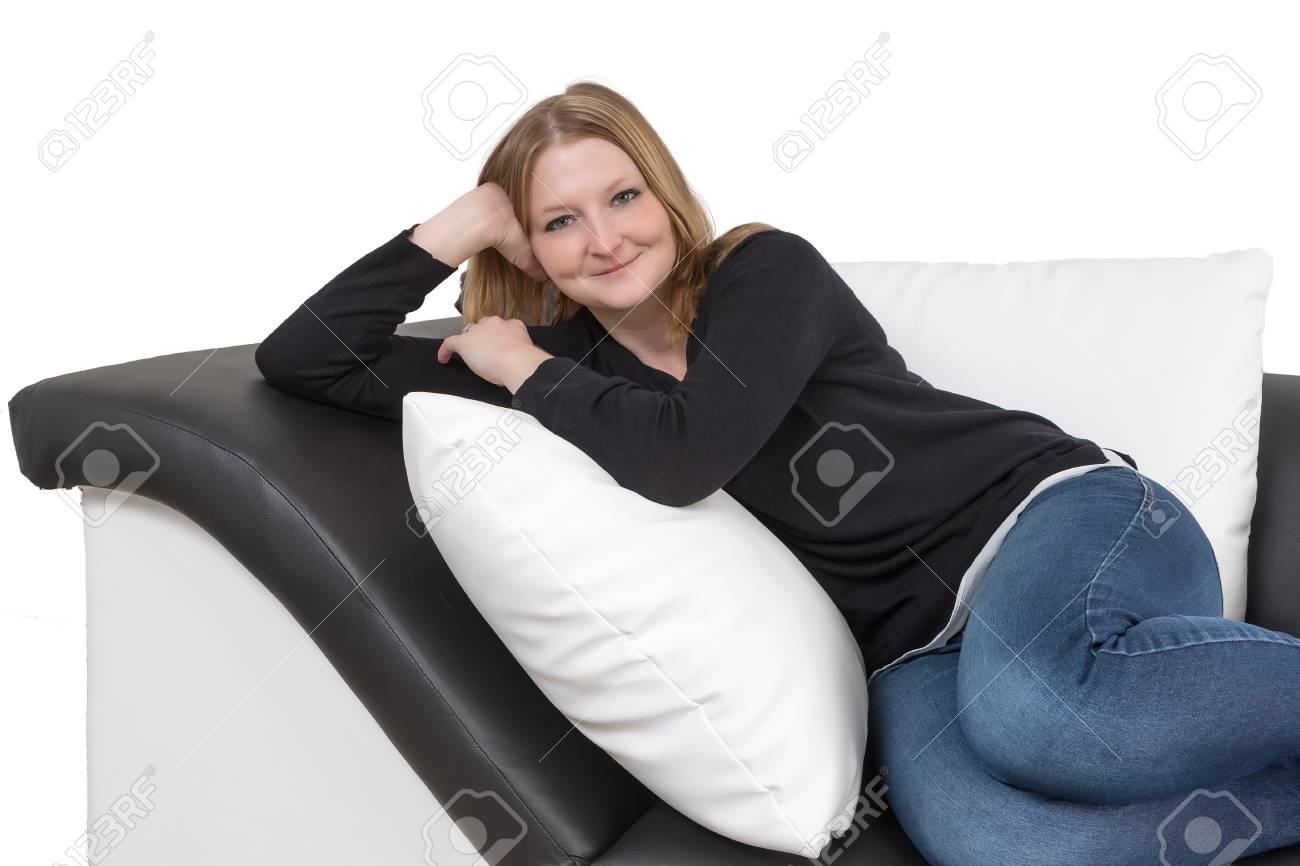 Divani Bianchi E Neri : Sorridente lungo giovane donna dai capelli è sdraiato su un divano