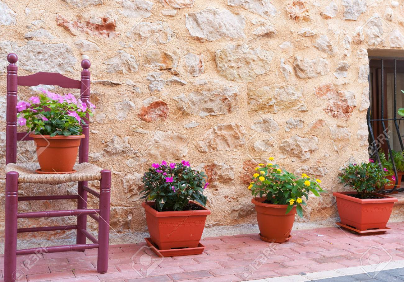Chair and flower pots decorate home exterior in narrow Spanish traditional village streets Stock Photo - & Chair And Flower Pots Decorate Home Exterior In Narrow Spanish ...