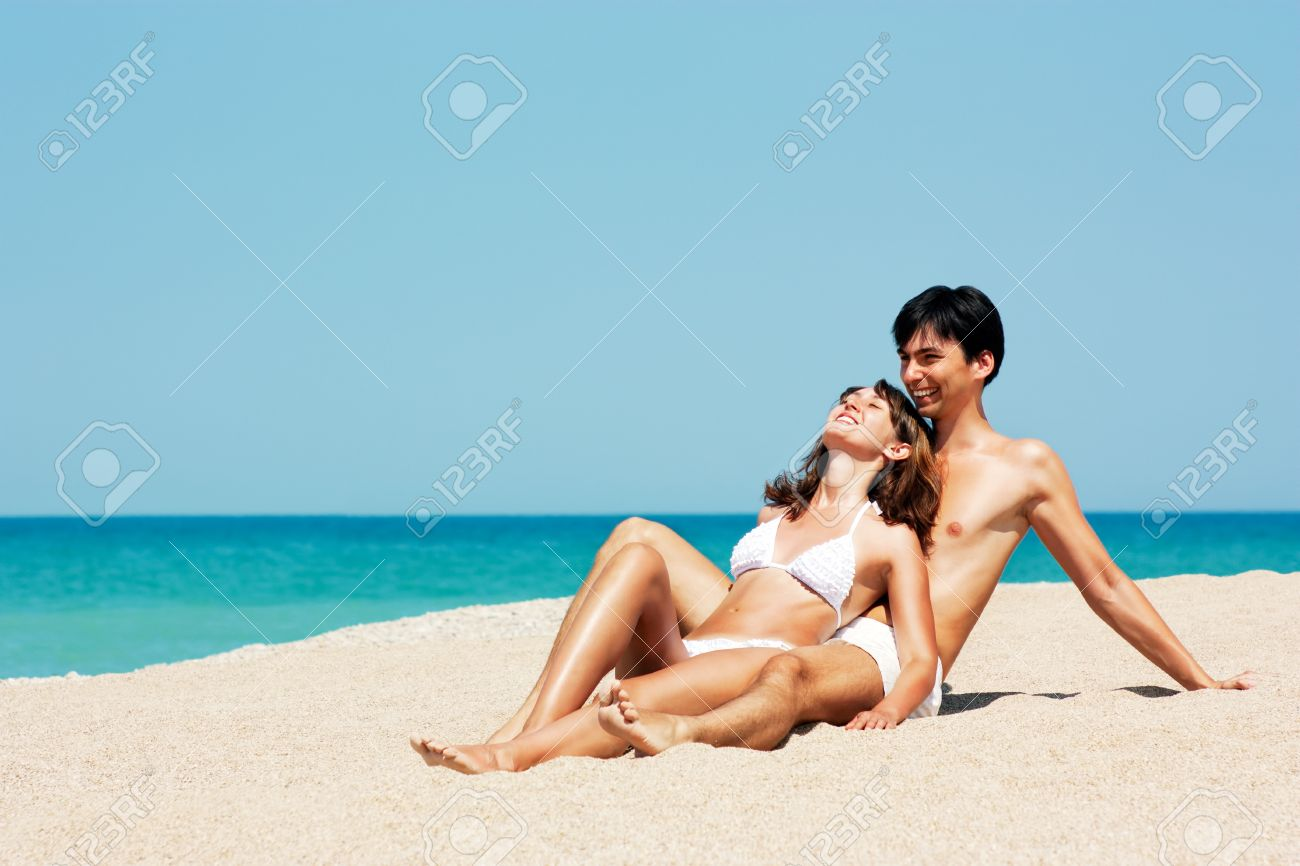 Happy Young Couple Lying on a Beach and Holding Each Other Stock Photo - 14830069