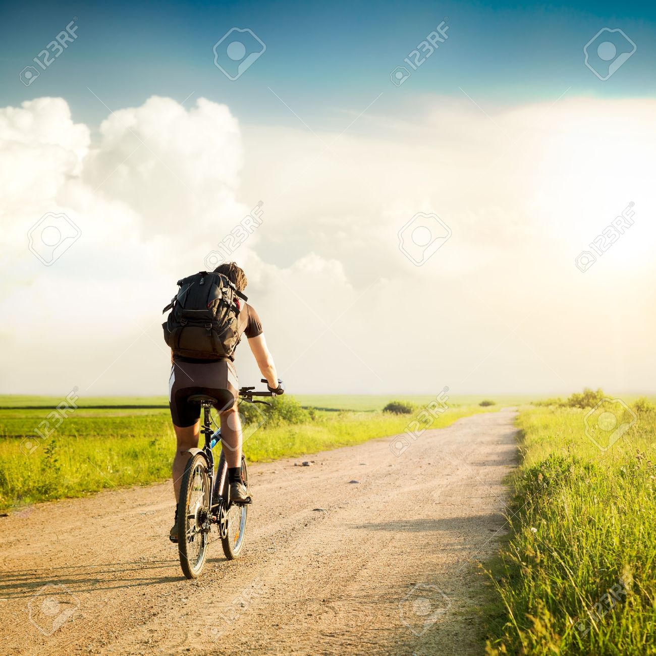 Rear View of a Man with Backpack Riding a Bicycle on Beautiful Nature Background. Healthy Lifestyle and Travel Concept. Styled Toned Photo. Copyspace. - 33651787