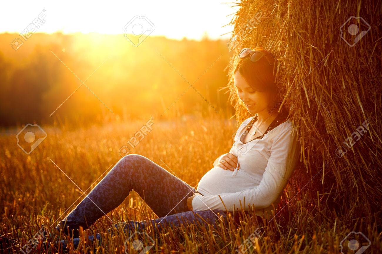 Young Pregnant Woman Sitting by the Haystack at Sunset and Embracing her Belly. 7 Month Pregnancy. Maternity Concept. Toned Photo. - 35965630