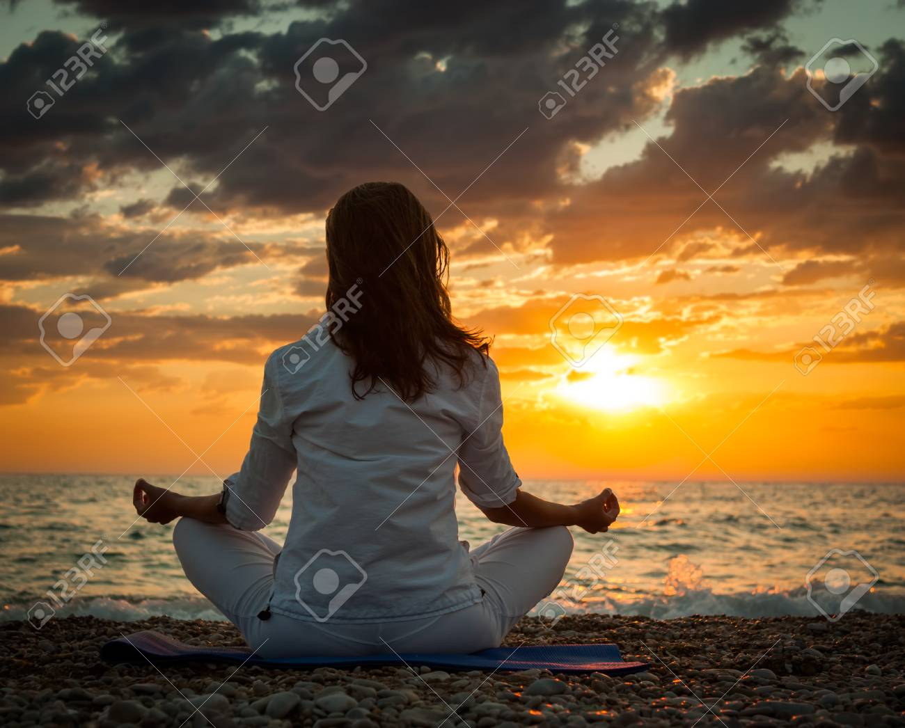 Woman Practicing Yoga by the Sea at Sunset. Rear View. Dramatic Sky. Healthy Lifestyle Concept. - 36892669
