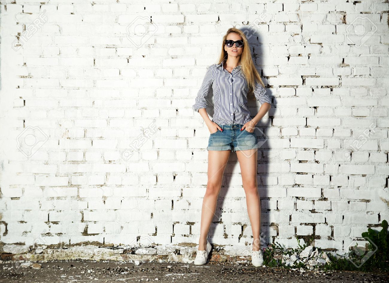 Full Length Portrait of Trendy Hipster Girl with Hands in Pockets on White Brick Wall Background. Trendy Urban Fashion Concept. Copy Space. - 38110443