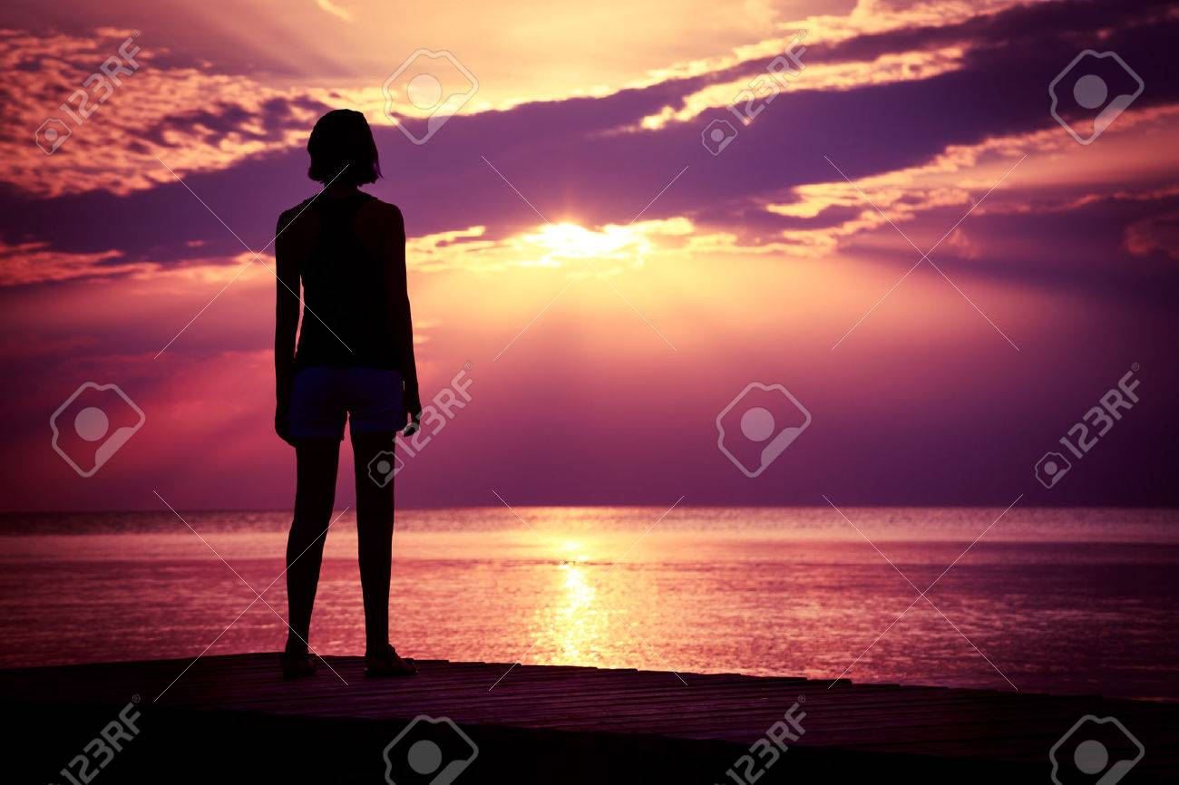 Silhouette of Young Woman Watching Sea Sunset. Breathtaking Nature Background. Toned Photo with Copy Space. - 38534367