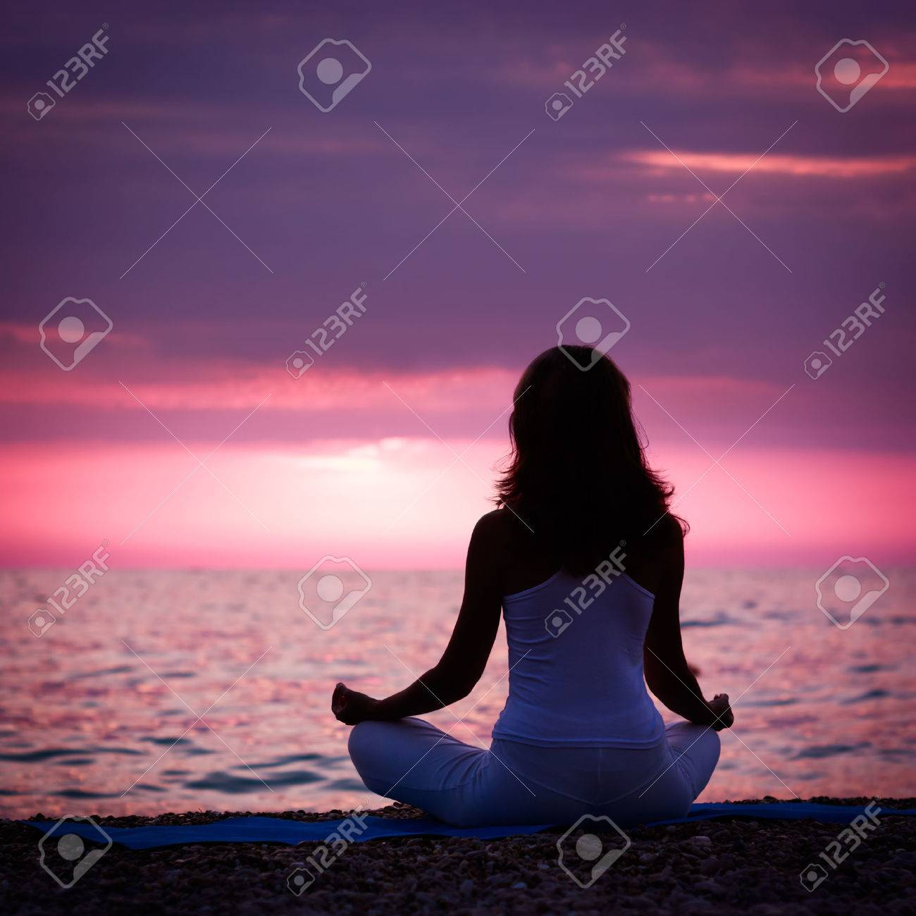 Silhouette of Woman Meditating in Lotus Position by the Sea at Sunset. Rear View. Nature Meditation Concept. - 38571906