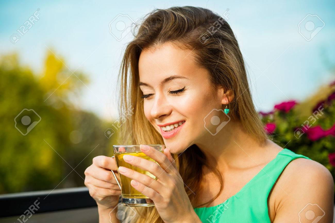 Young Happy Woman Drinking Green Tea Outdoors. Summer Background. Shallow Depth of Field. Healthy Nutrition Concept. - 39225146