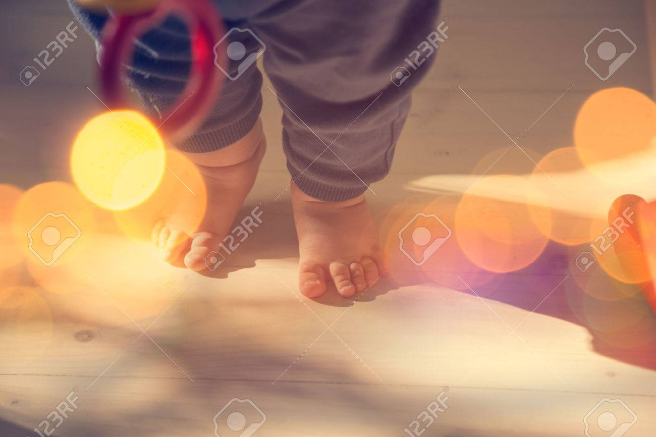 Small Baby Feet on Wooden Floor. First Steps Concept. Shallow Depth of Field. Toned Photo with Bokeh and Copy Space. - 47917490