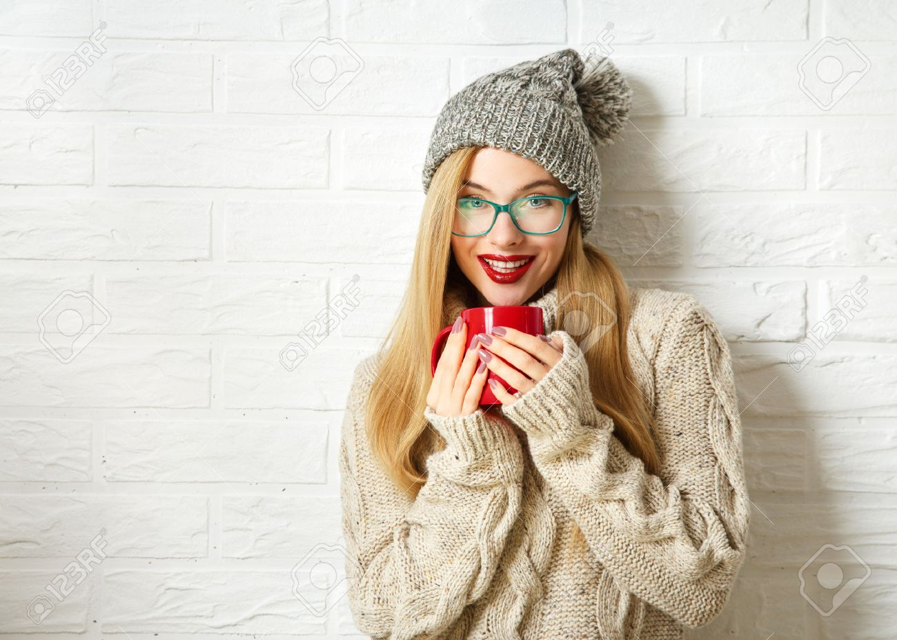 Smiling Hipster Girl in Knitted Sweater and Beanie Hat with Mug in Hands at  White Brick 33d6042e782