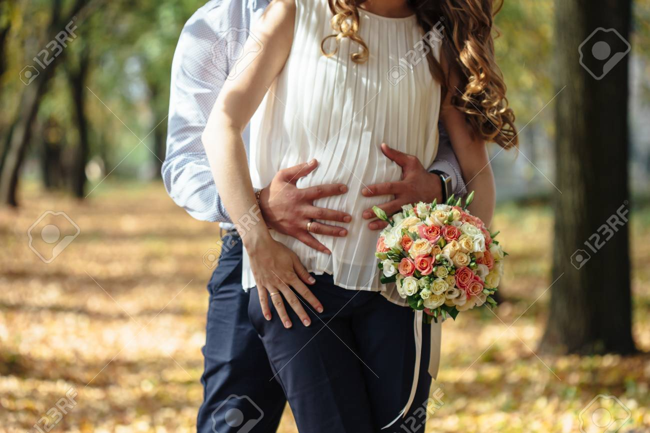 6d21778f1 Feliz novia embarazada y el novio la celebración de ramo de la boda. El  novio