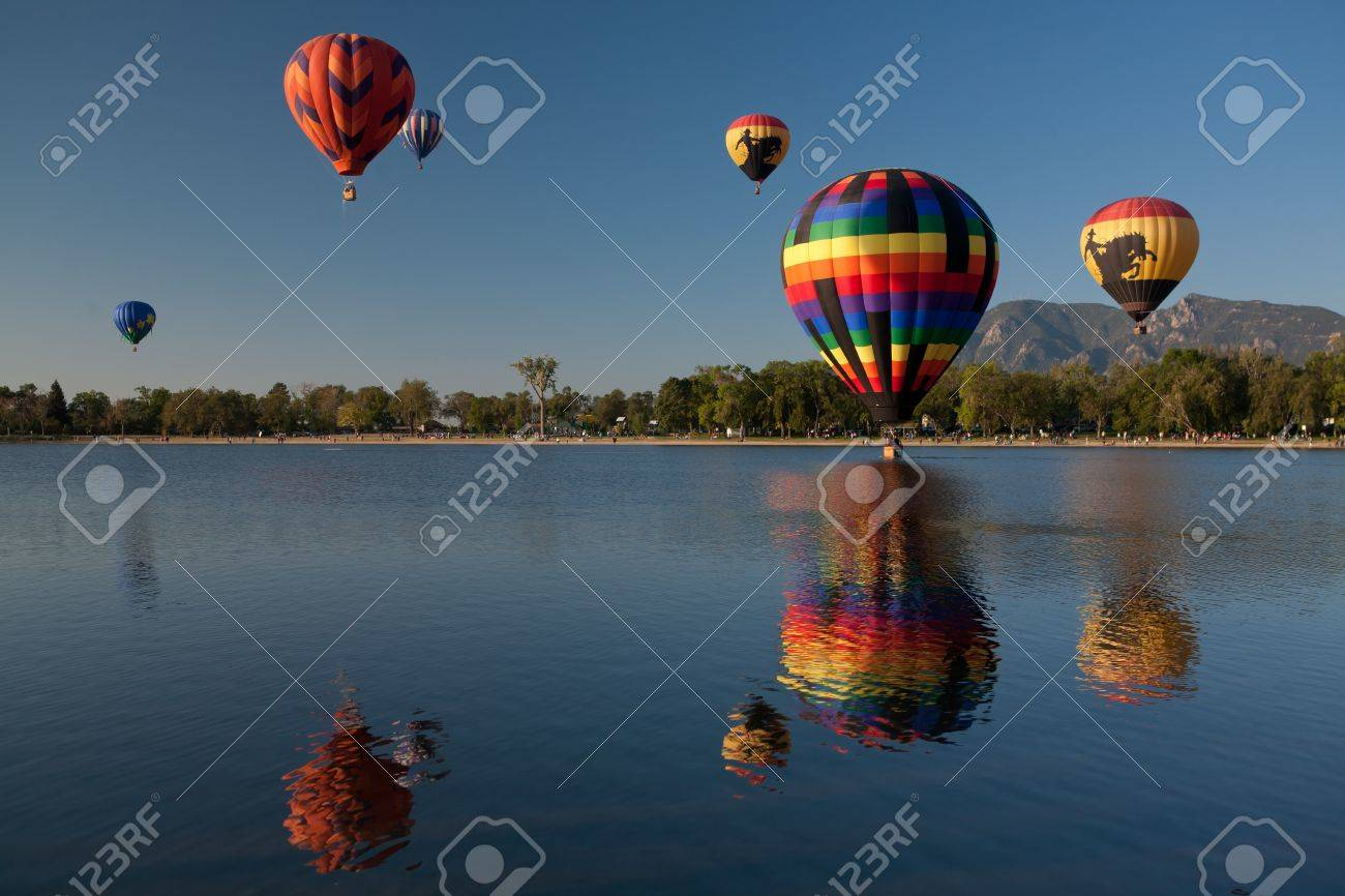 Colorful Hot Air Balloons Reflected in a Lake with Rocky Mountains and Clear Blue Skies Stock Photo - 18986428