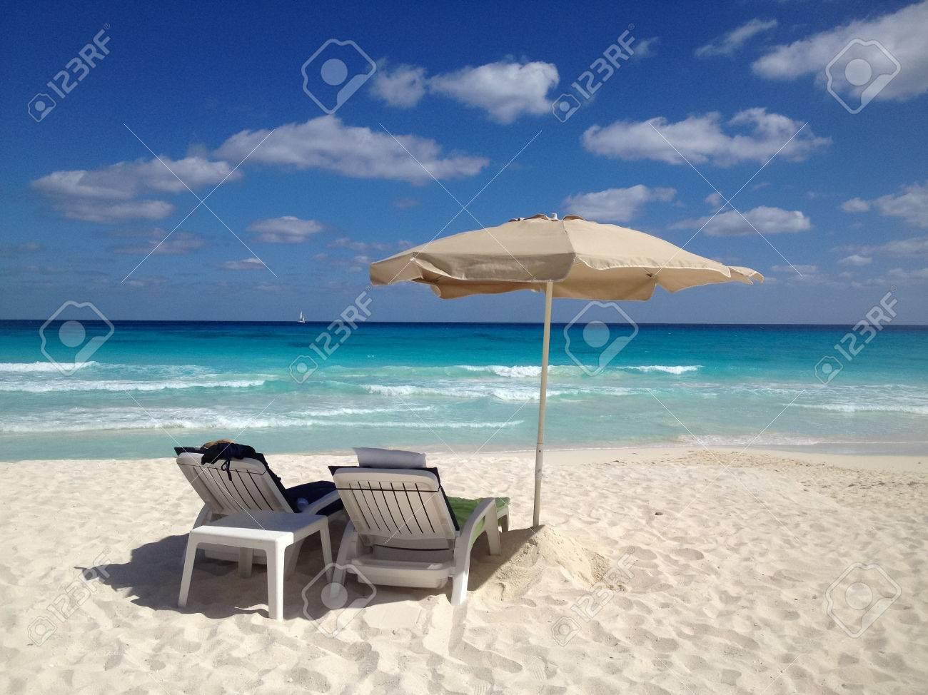 Due sedie a sdraio su una spiaggia di sabbia bianca con ombrellone ...