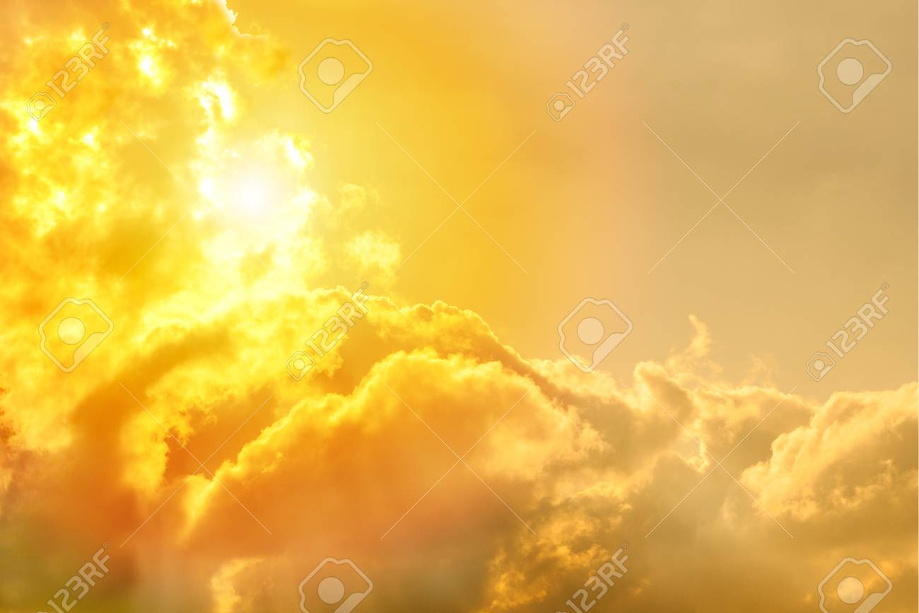 fluffy cumulus clouds in the sunlight toned background