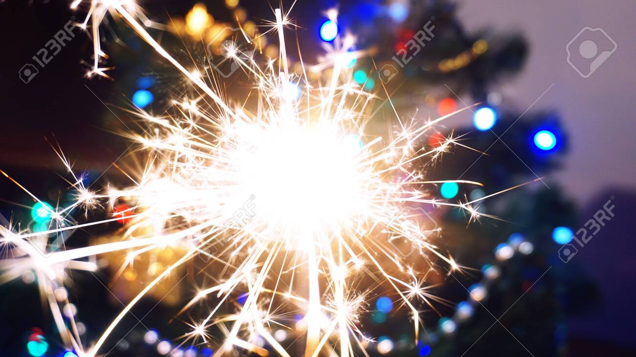 Sparkler - blurry background. Christmas lights, new year concept,..