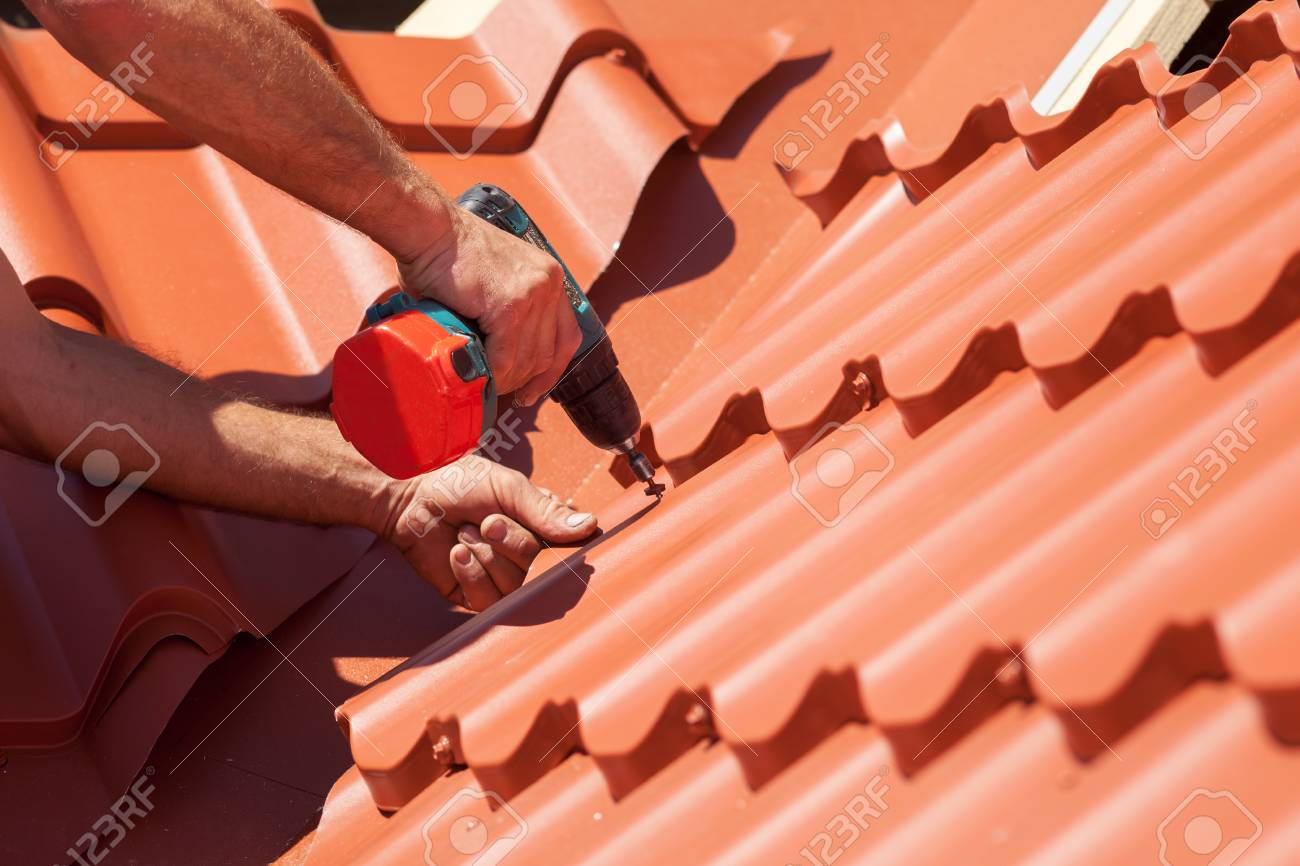 Worker on a roof with electric drill installing red metal tile on wooden house - 76578093