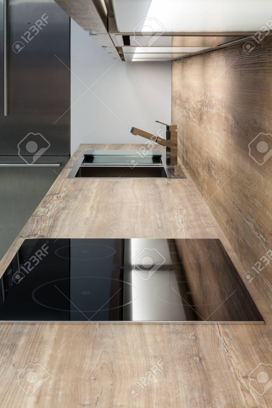 New modern kitchen with exhaust hood and counter top made of..