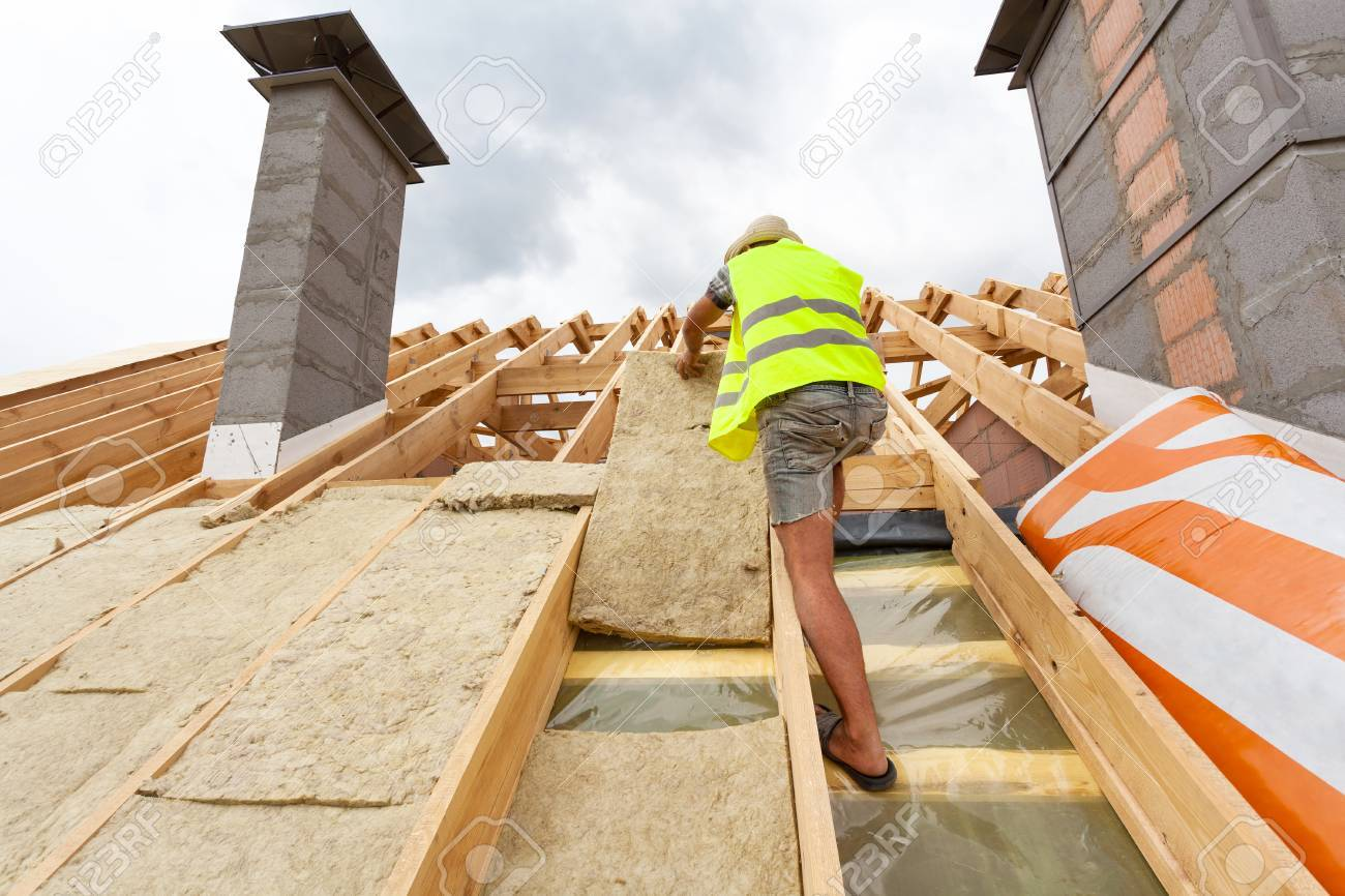 Roofer builder worker installing roof insulation material (rockwool) on new house under construction - 82833391