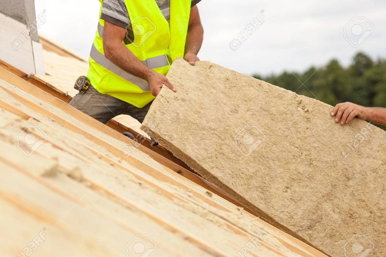Roofer builder worker installing roof insulation material on new house under construction - 83284009