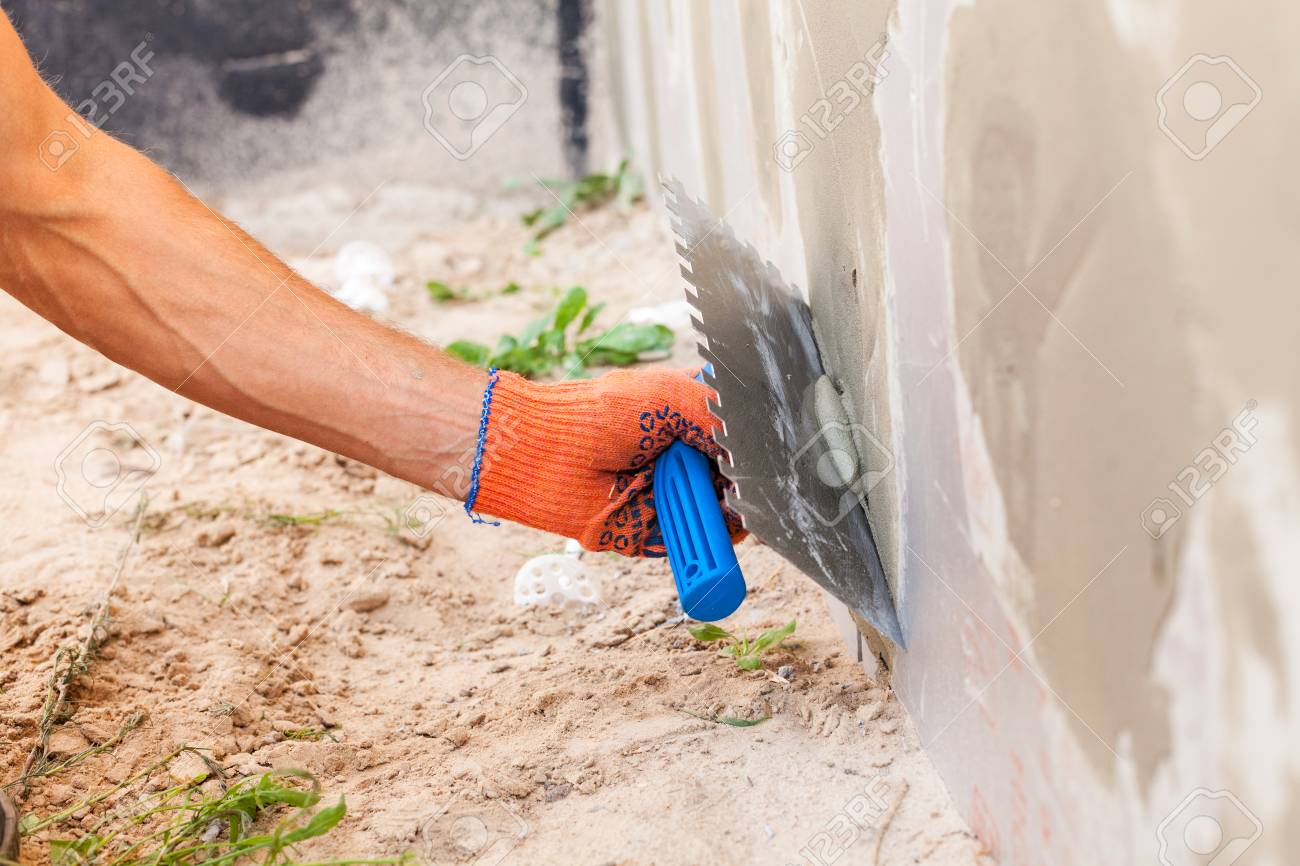 Construction worker plastering a wall and house foundation with trowel - 83284028