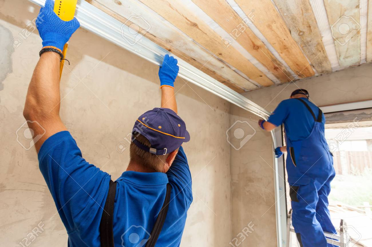 Garage doors installation. Workers installing Post Rail and Spring Installation / Assembly. - 85889042