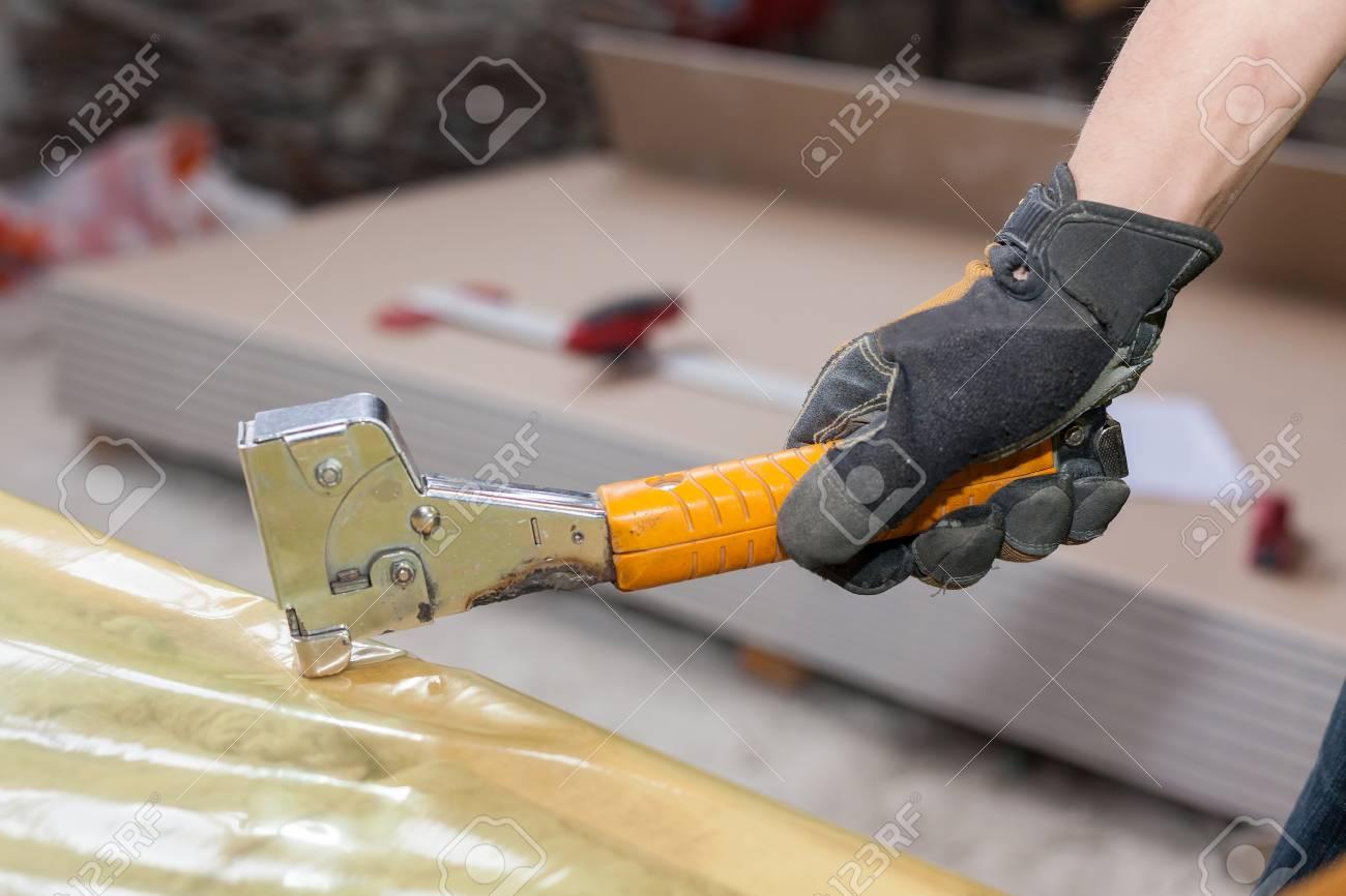Building A Wall For Frame House. Worker Installing Vapor Barrier ...