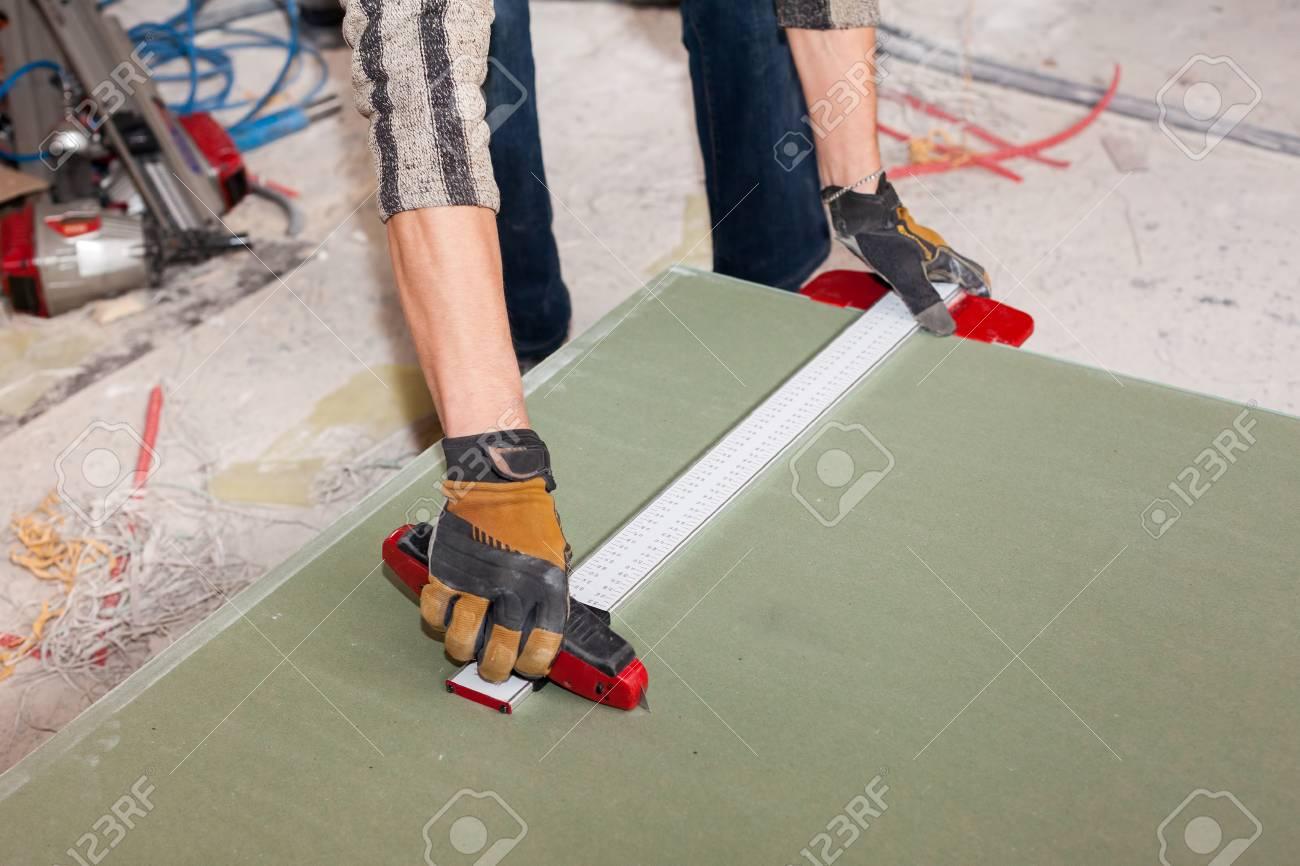 Eine Wand Für Rahmenhaus Errichten. Arbeiter Schneidet Trockenbau ...