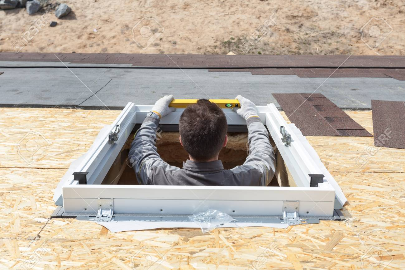 Worker on a asphalt shingle roof installing new plastic (mansard) or skylight window - 87780962
