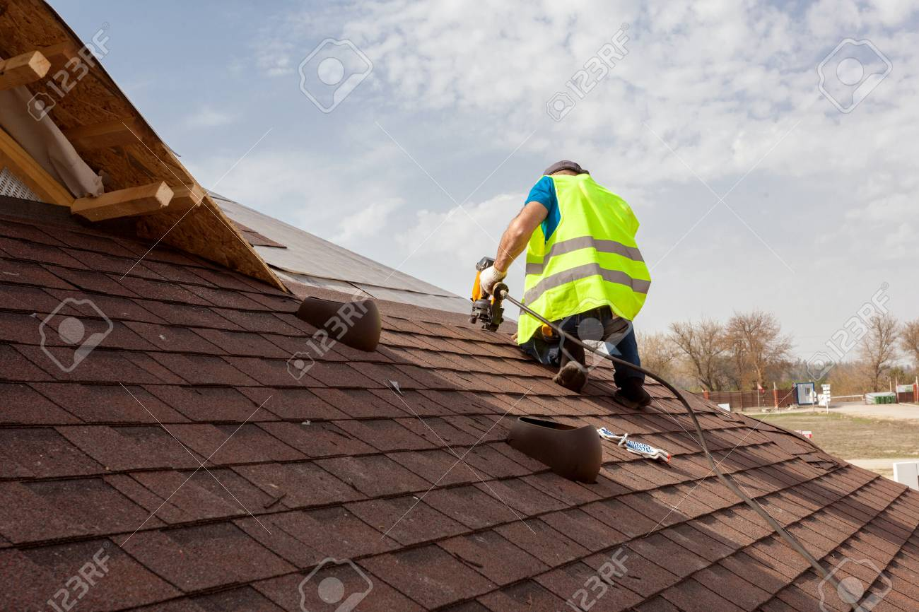 Construction worker putting the asphalt roofing (shingles) with nail gun on a large commercial apartment building development - 88262805