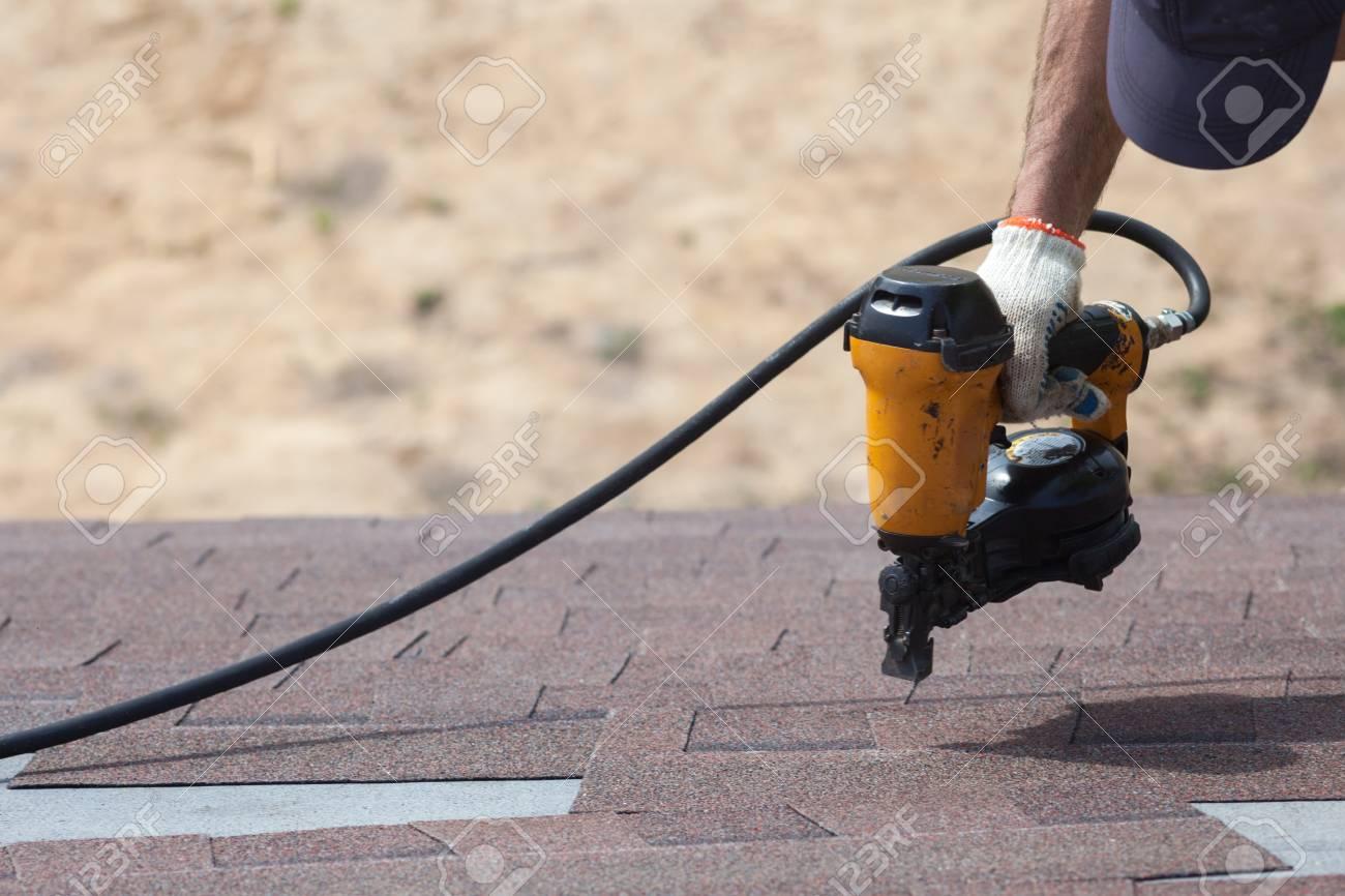 Roofer builder worker with nailgun installing Asphalt Shingles or Bitumen Tiles on a new house under construction - 88263061