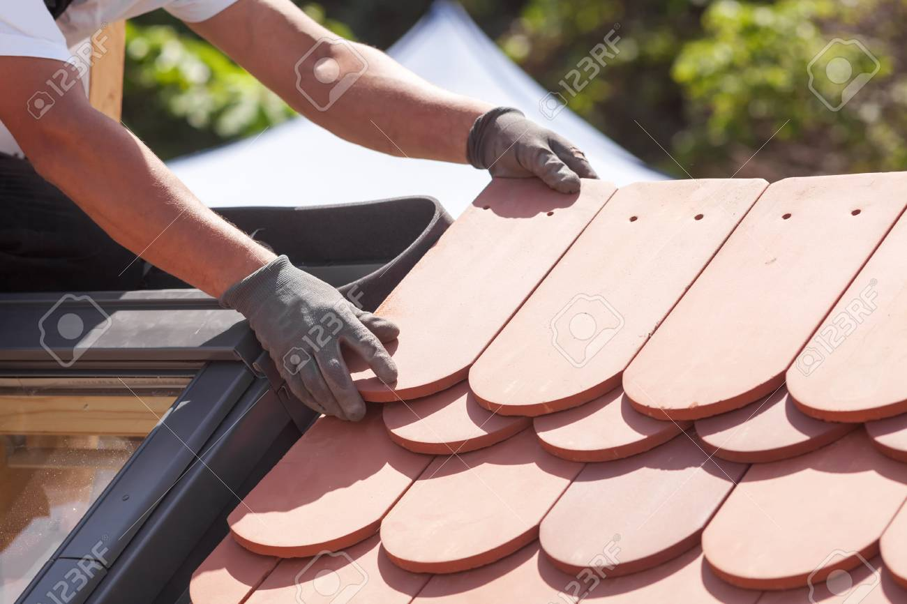 Hands of roofer laying tile on the roof. Installing natural red tile. - 88649630