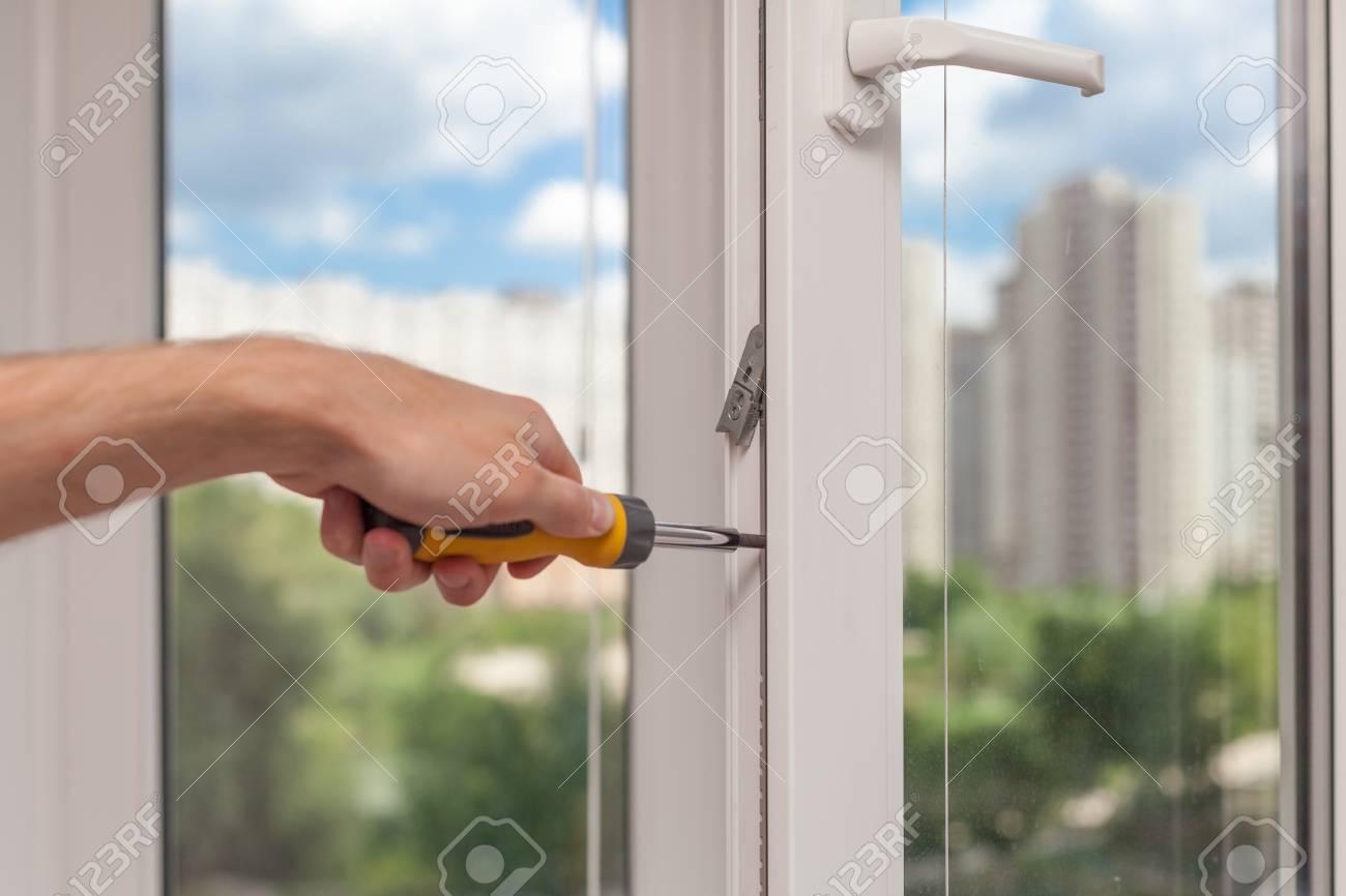 Handyman repairs plastic window with screwdriver - 92630069