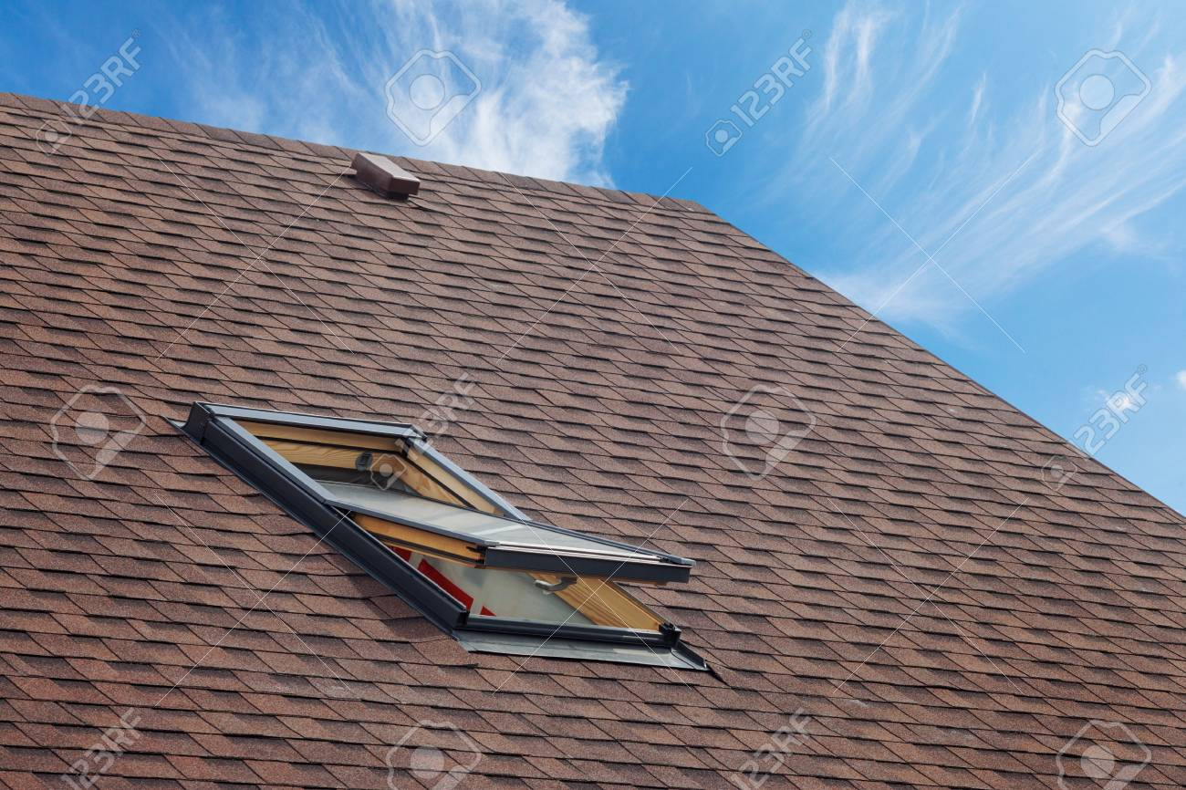 Roof with mansard windows and asphalt shingles.Open skylight on a roof shingles under construction - 95118421