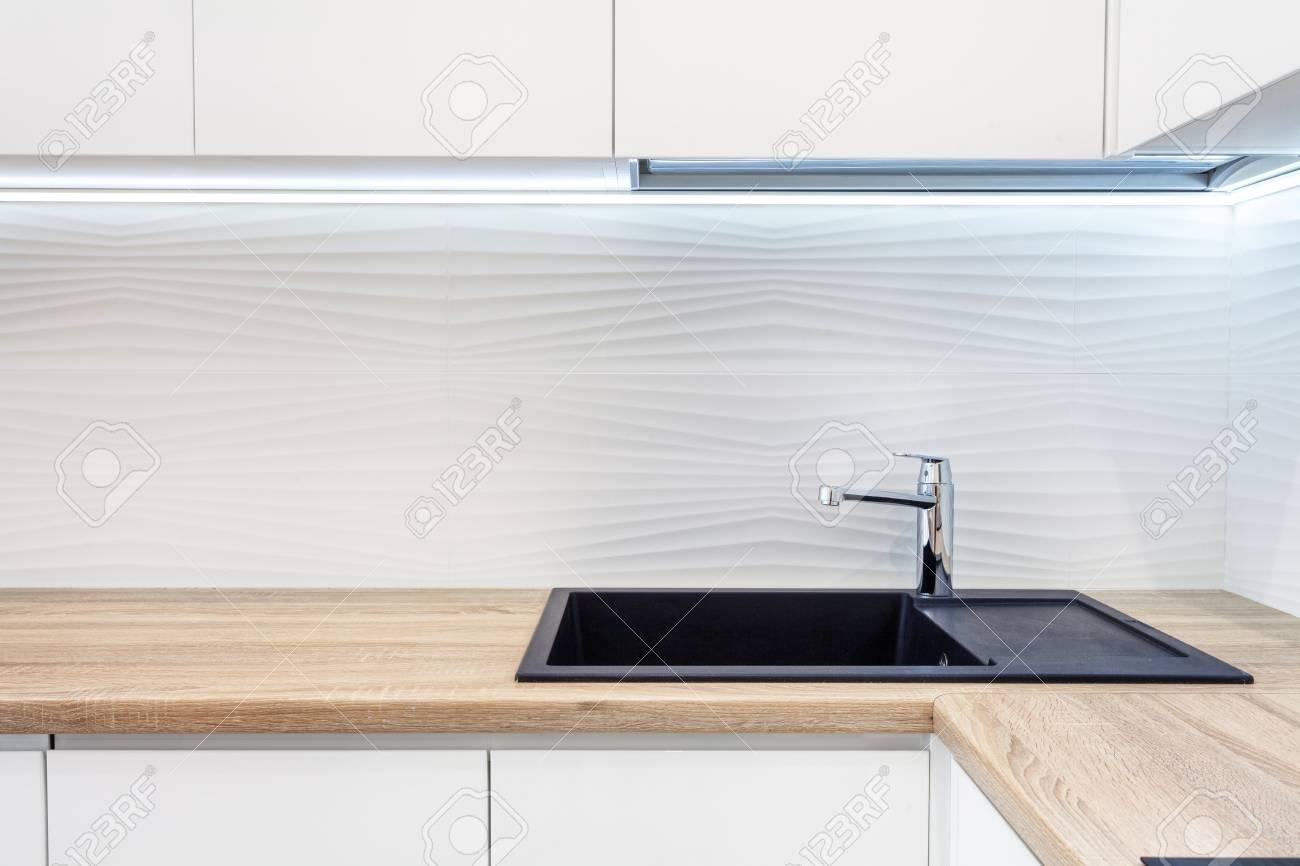 Modern designer chrome water tap over black new kitchen sink...
