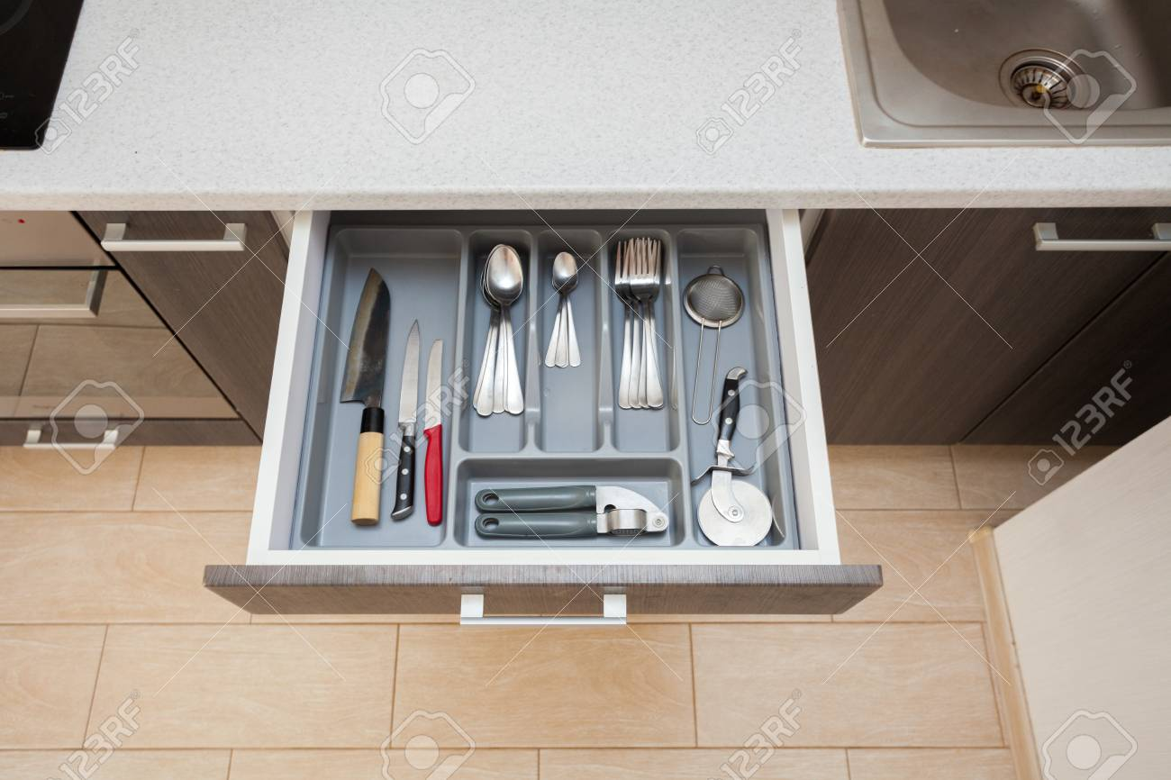 High angle top view photo of clean white cook worktop table and open new modern wooden kitchen drawer with different cutlery spoon, knife, fork and stuff - 108812399