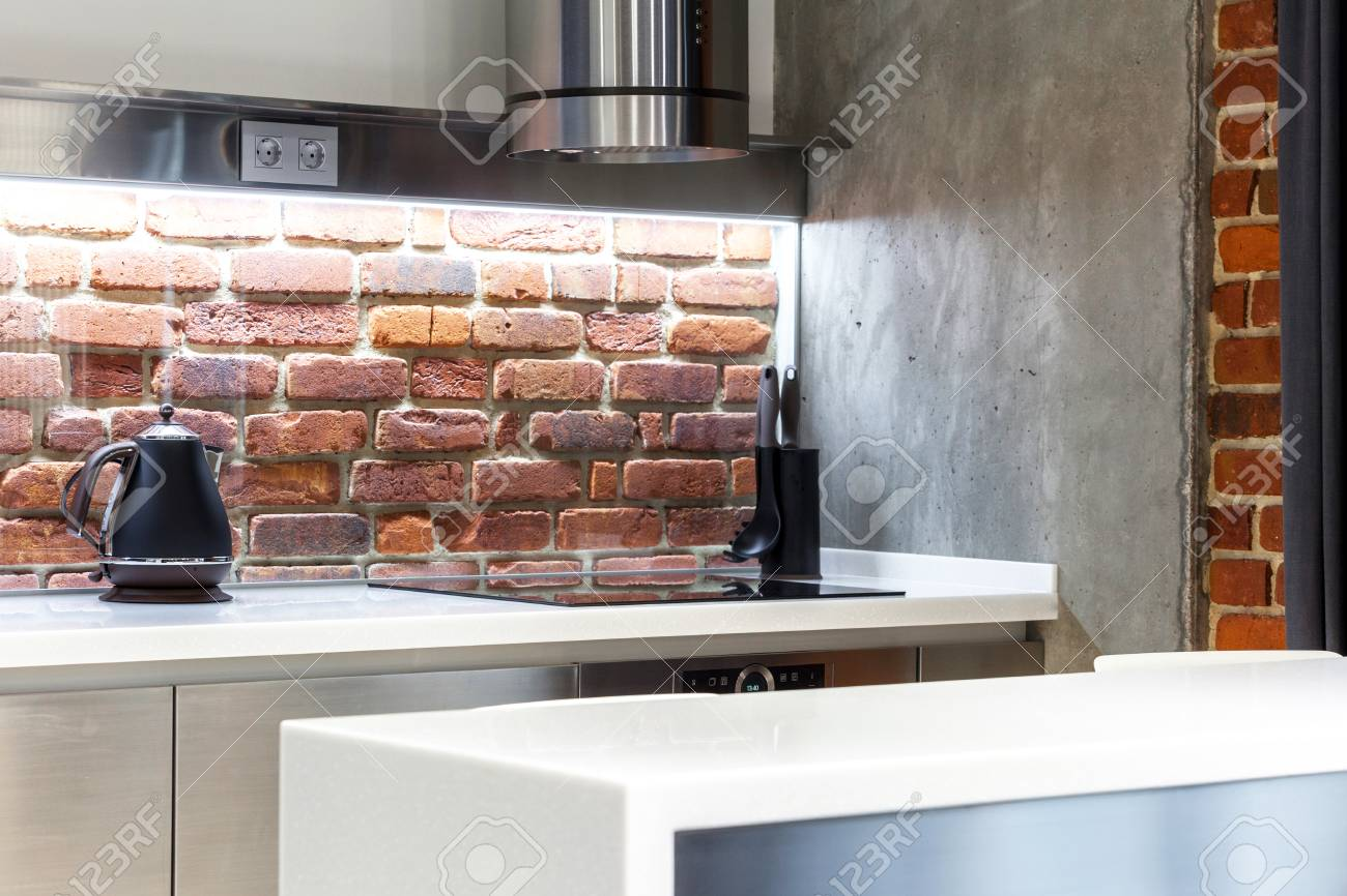 Element of loft kitchen with red brick wall, light and different..