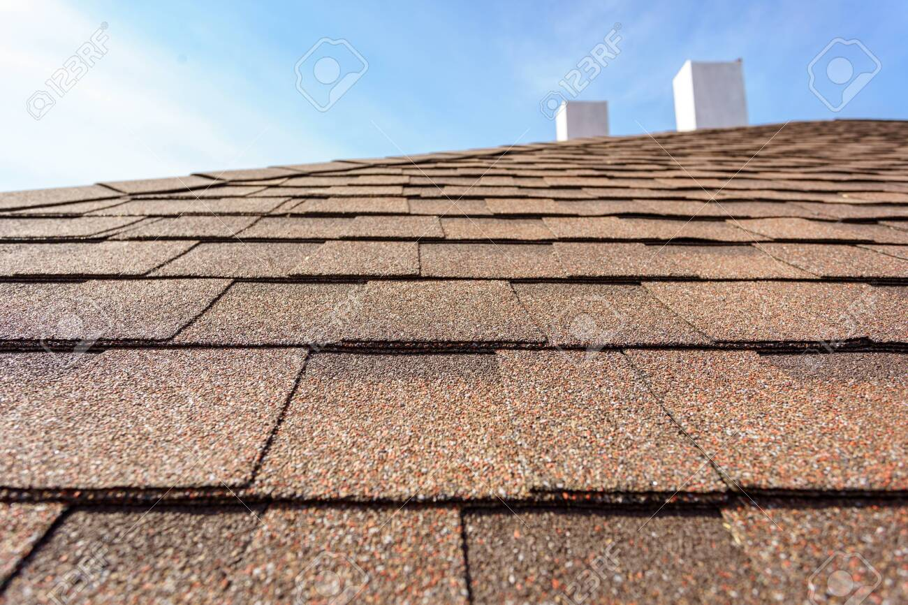 Close up photo layer of new asphalt shingles on roof top of new house under construction with chimney and blue sky on blurred background - 128529535